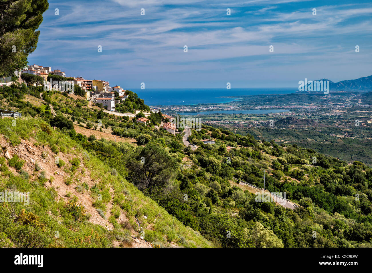 Town of Baunei, with town of Tortoli at Tyrrhenian Sea coast far in distance, Nuoro province, Sardinia, Italy - Stock Image