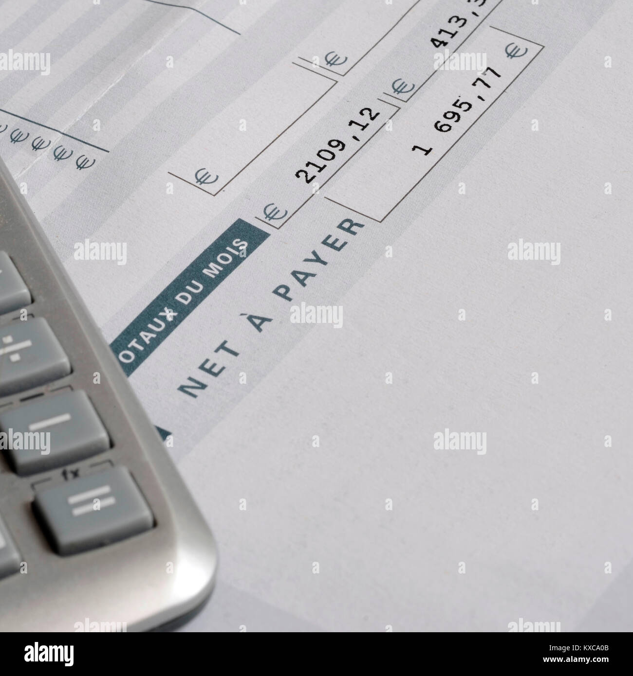 euro pay slip and calculator close up for payroll or salary stock