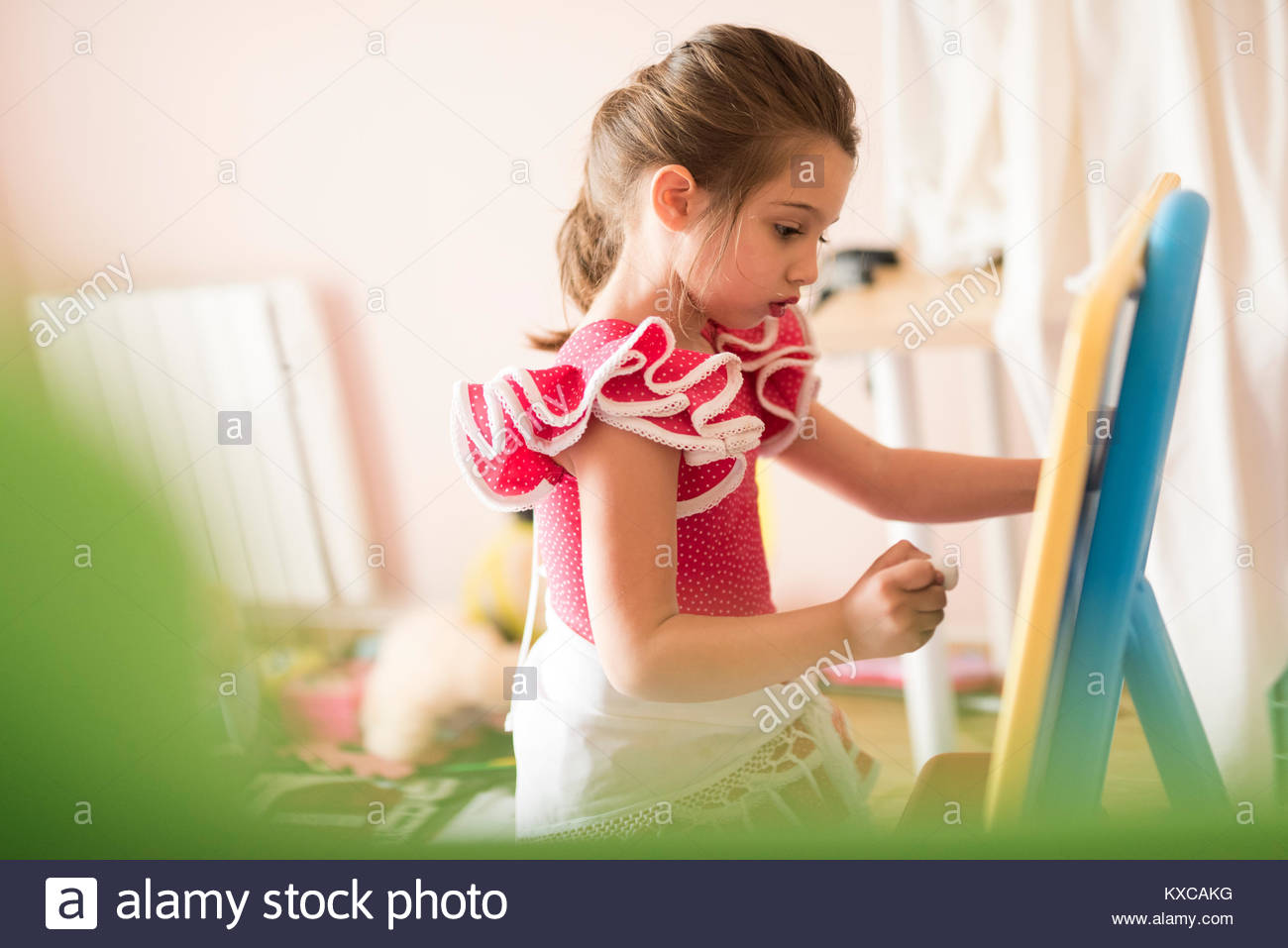 Little girl drawing on chalk board in children's room - Stock Image