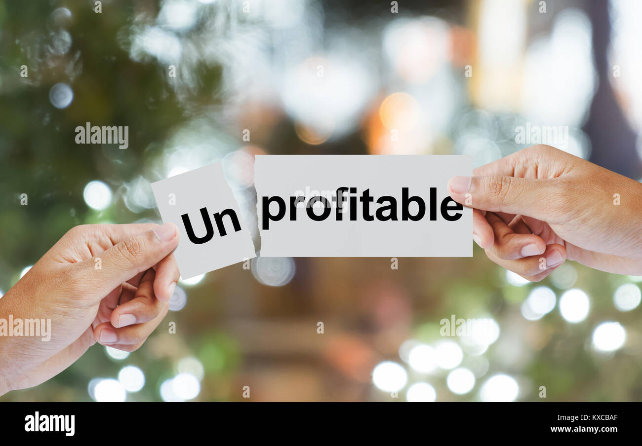 hand tear wording unprofitable on paper in two pieces with bokeh background - Stock Image