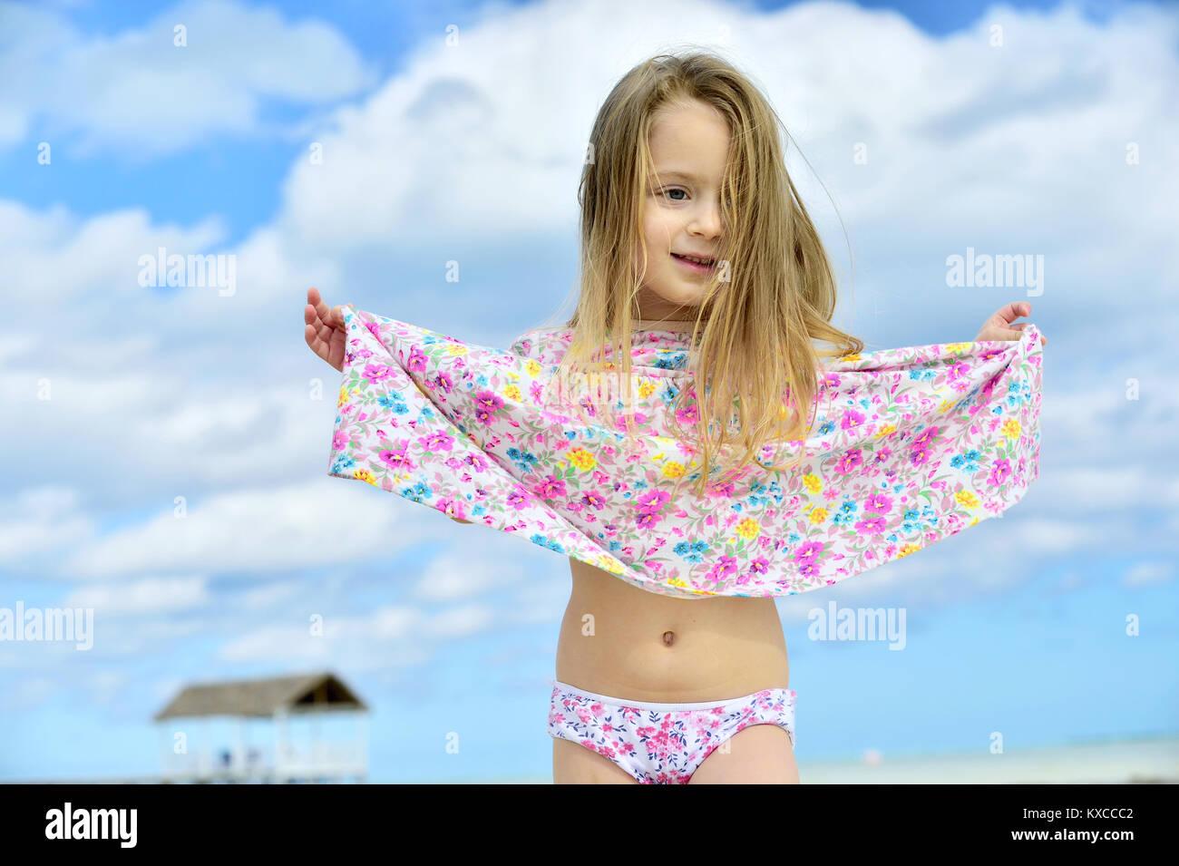 Cute Little Girl On Sandy Beach Blue Sky Background