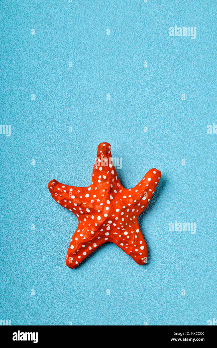 a handmade papier-mache starfish on a blue background with a blank space on top - Stock Image
