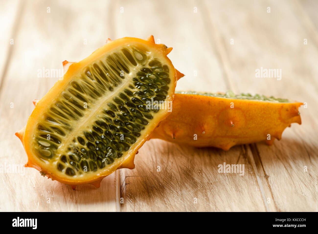 closeup of a kiwano or horned melon cut in halves on a white rustic wooden table - Stock Image