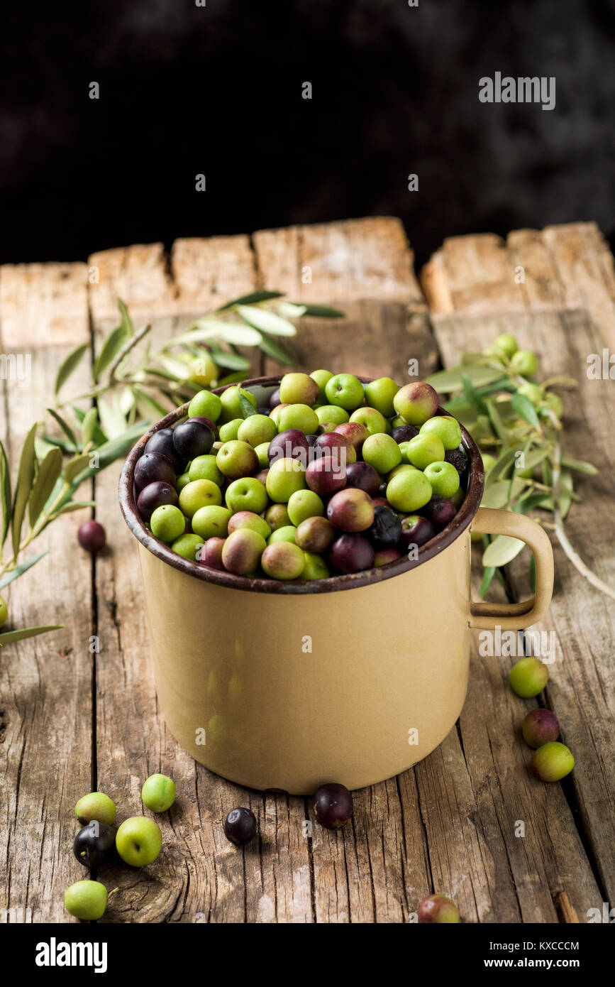 a handled enamelware pot full of arbequina olives from Catalonia, Spain, on a wooden rustic table, against a dark - Stock Image