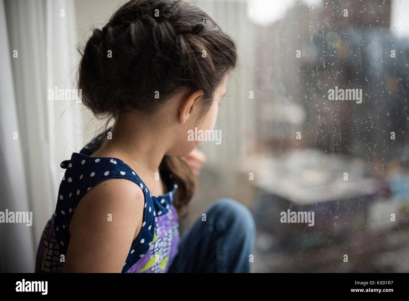 Thoughtful girl looking though wet window at home - Stock Image