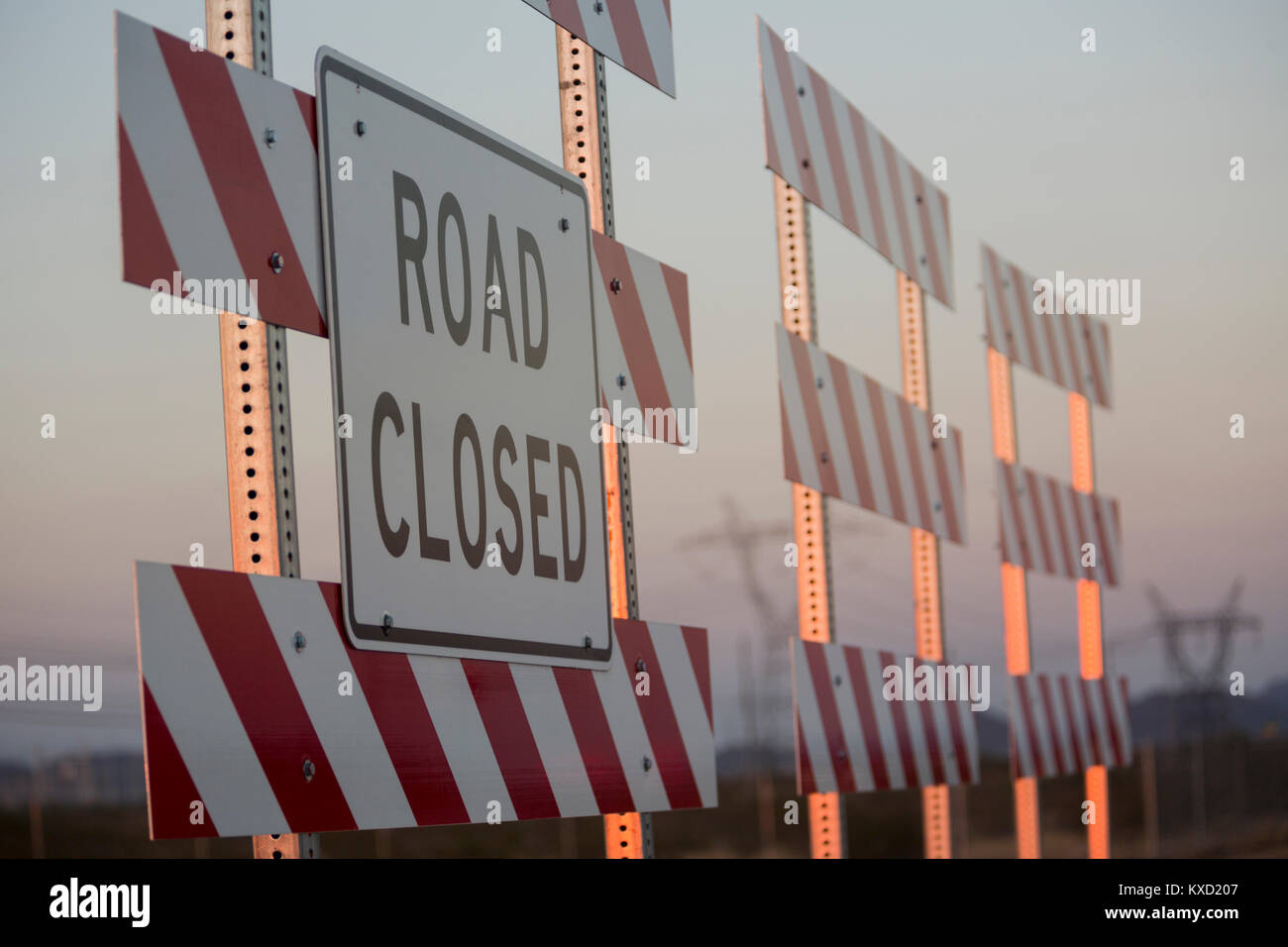 Road closed sign on barricade against sky during sunset - Stock Image