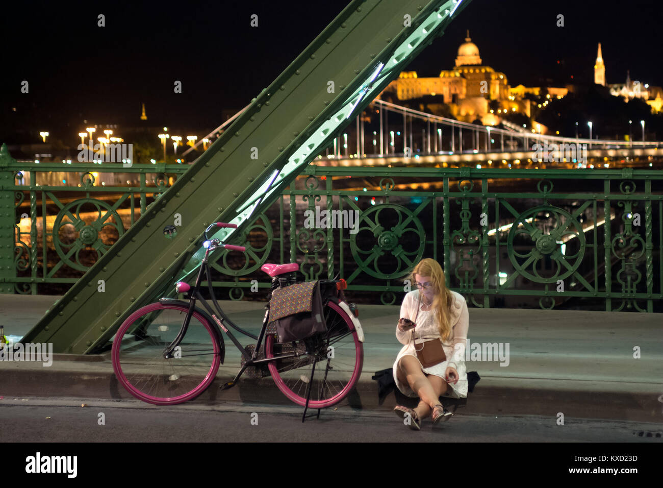 Girl sitting looking at mobile phone screen on sidewalk border beside rose bicycle. Liberty bridge, Budapest - Stock Image