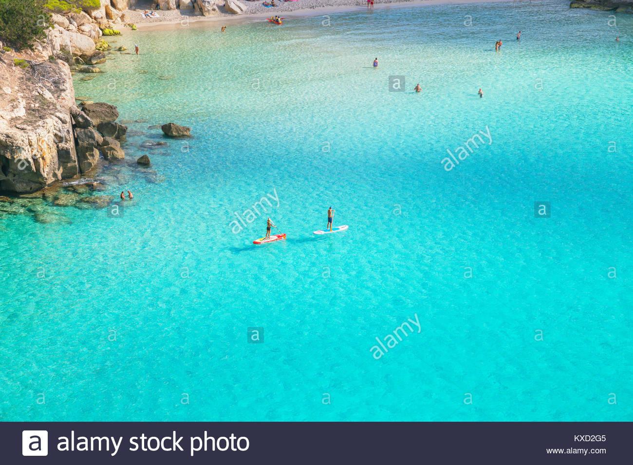 People paddleboarding on the emerald waters of Cala Mitjana,  Menorca, Balearic Islands, Spain - Stock Image