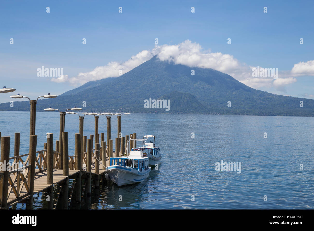 Boats moored by pier on Lake Atitlan against mountains and cloudy sky - Stock Image
