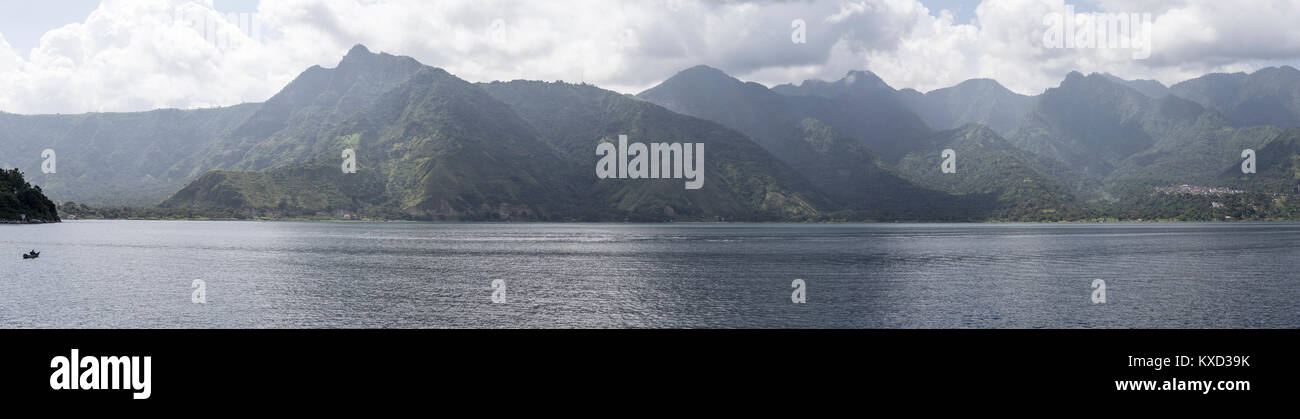 Panoramic view of Lake Atitlan against mountains and cloudy sky - Stock Image