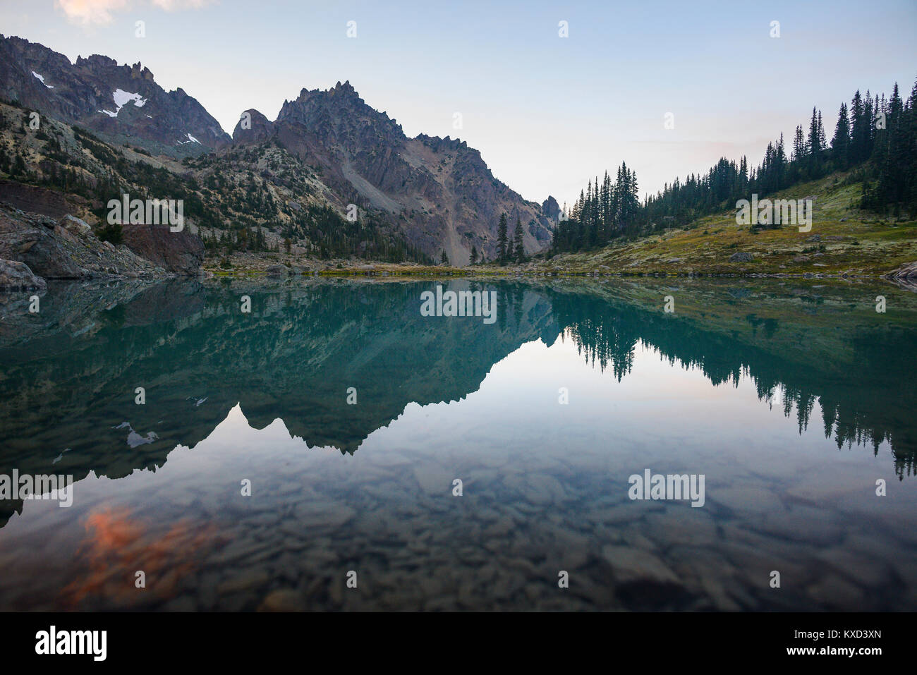 Symmetry view of lake by mountains against cloudy sky at Olympic National Park - Stock Image