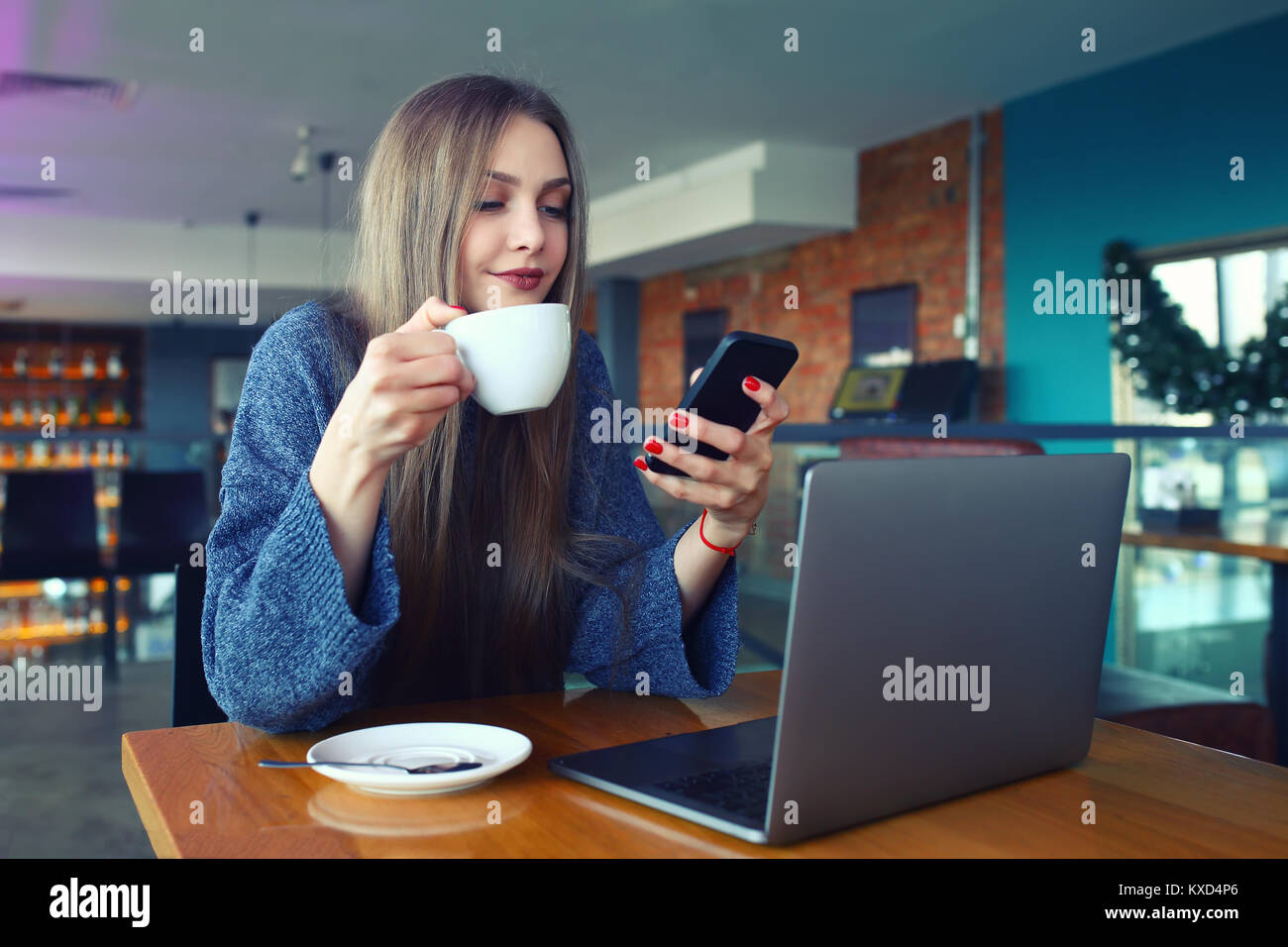 Woman typing text message on smart phone in a cafe. Young woman sitting at a table with a coffee using mobile phone. - Stock Image