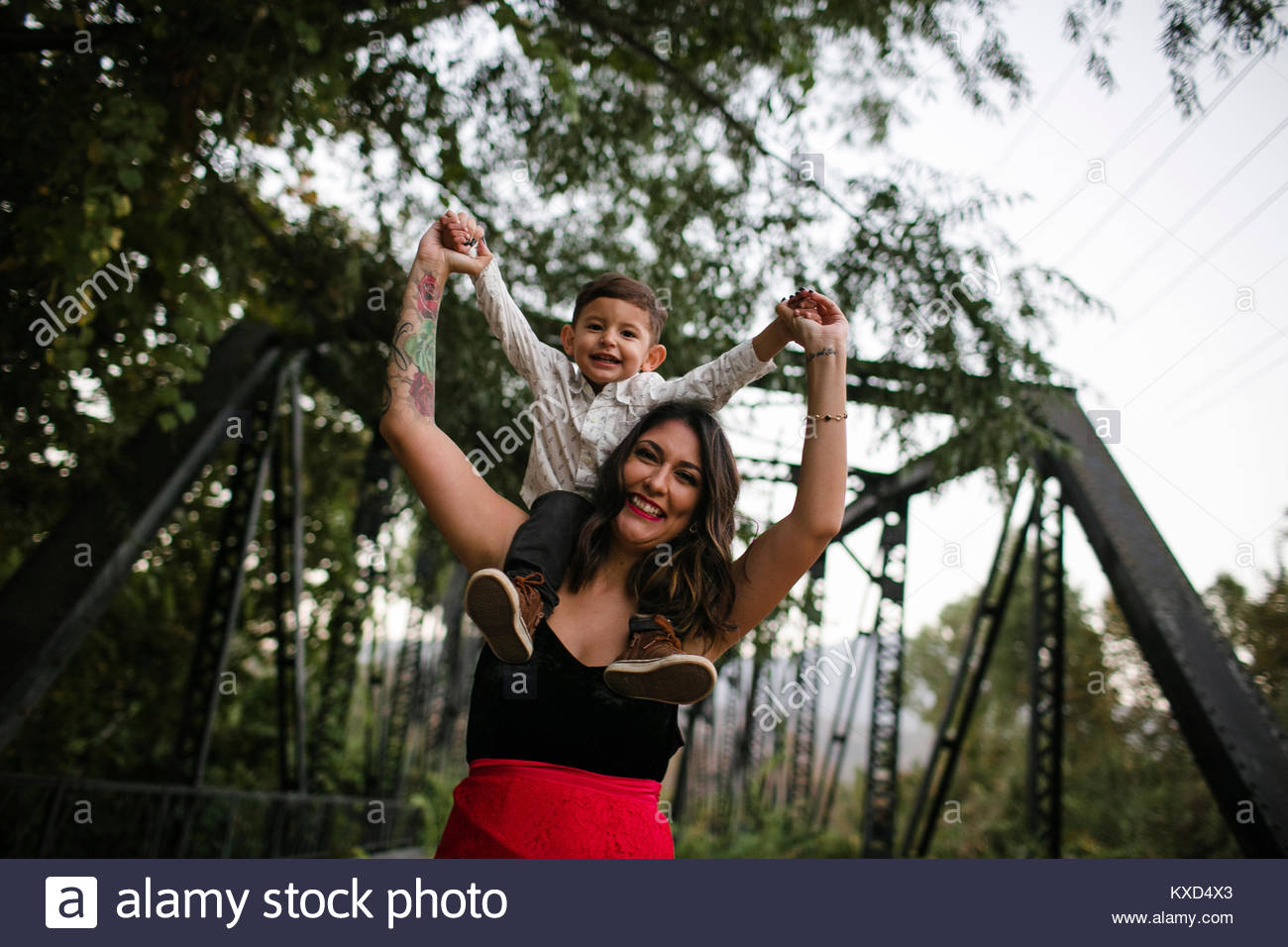 Portrait of happy mother and son on bridge - Stock Image