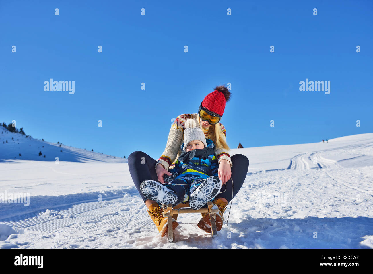 photo of happy mother and child playing in the snow with a sledge in a sunny winter day - Stock Image