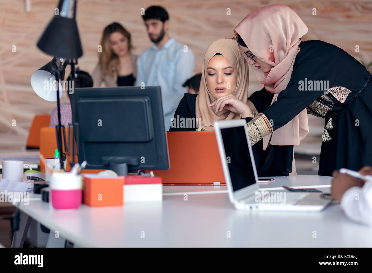 Business colleagues in hijabs looking at the computer monitor - Stock Image