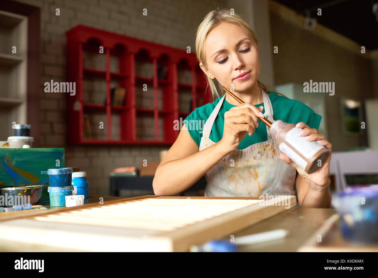 Pretty Young Woman Working in Art Studio - Stock Image