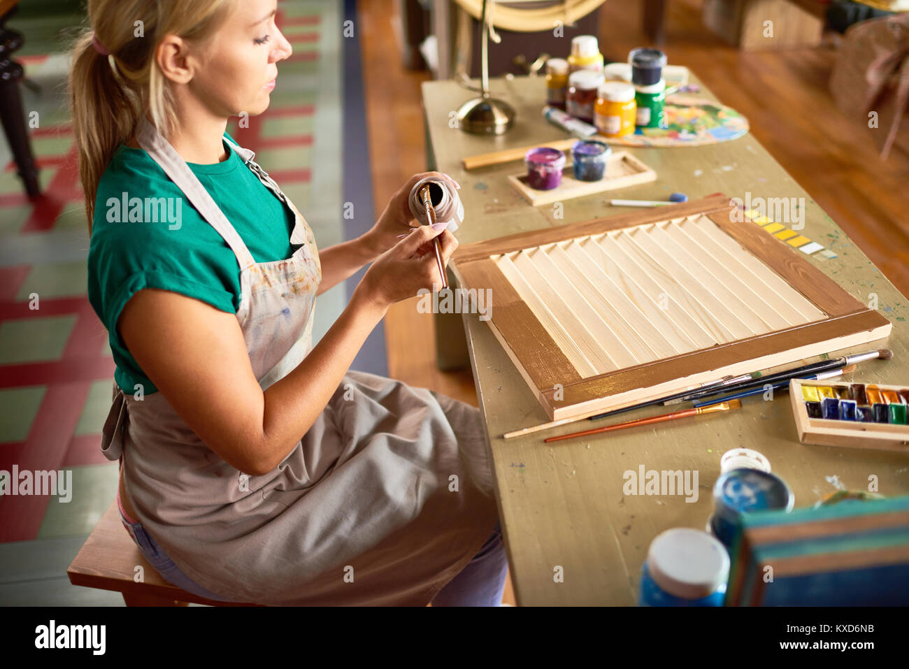 Young Female Artist Working in Studio - Stock Image