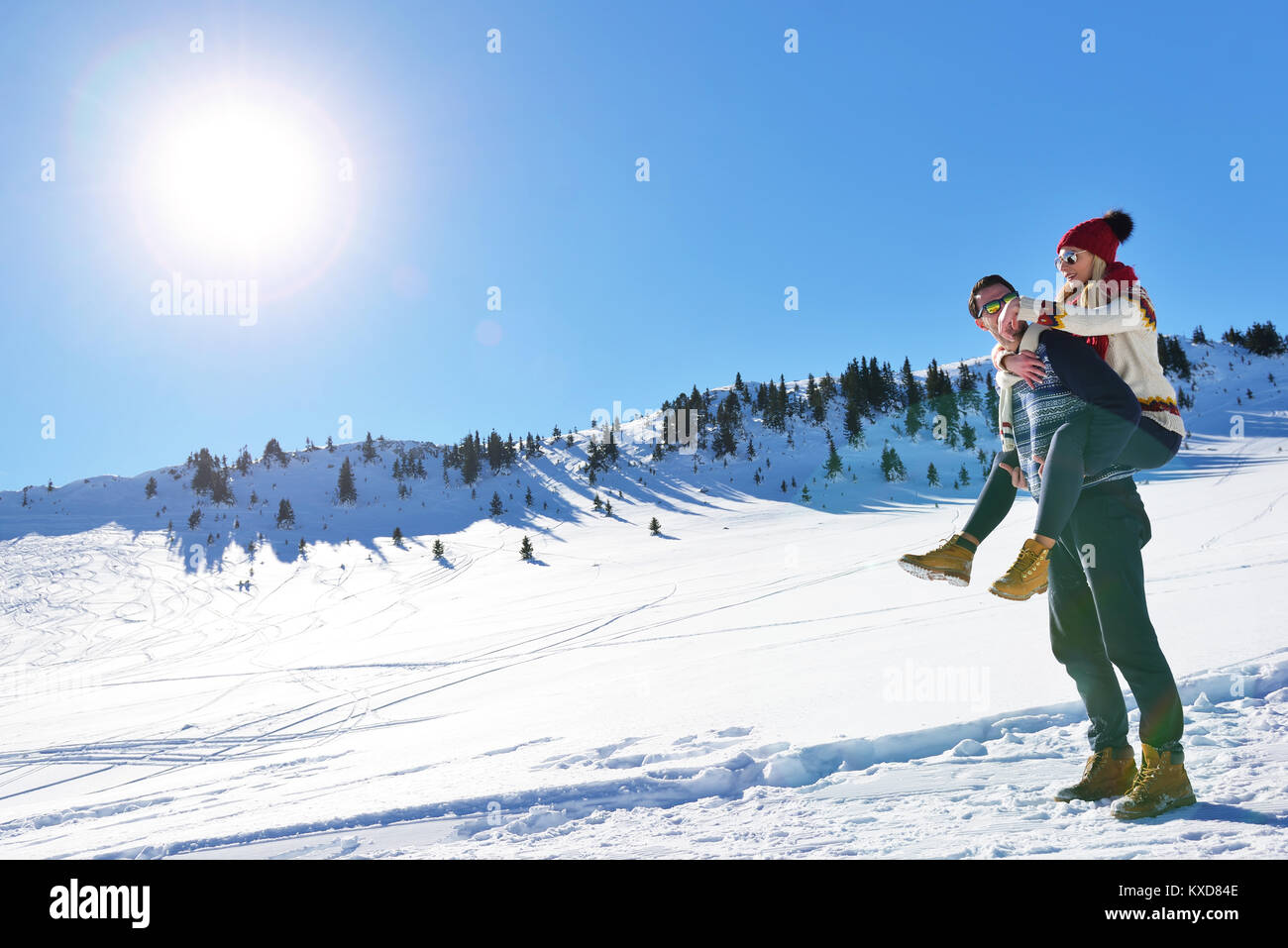Young couple having fun on snow. Happy man at the mountain giving piggyback ride to his smiling girlfriend. - Stock Image
