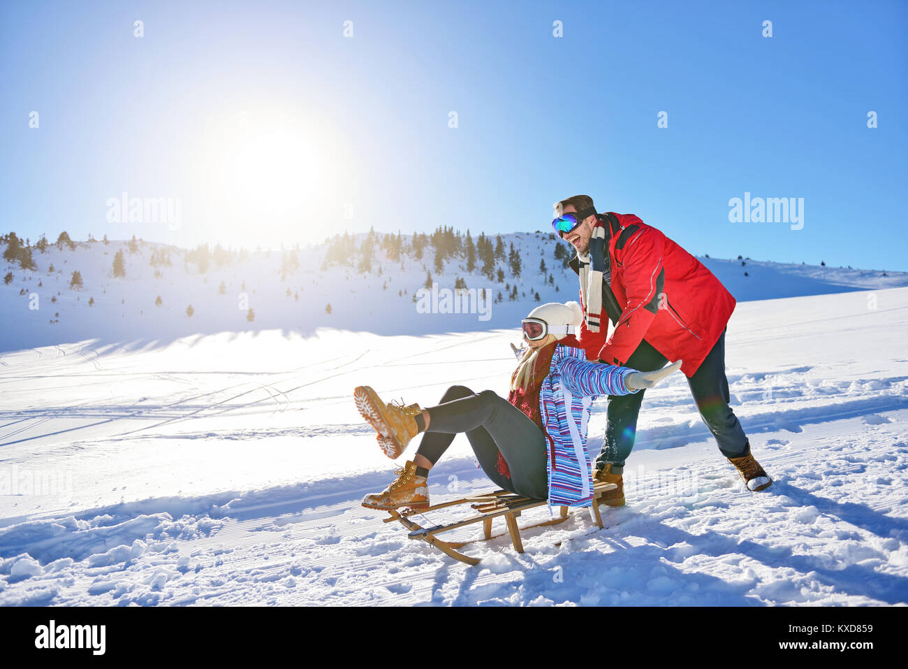 Young Couple Sledding And Enjoying On Sunny Winter Day - Stock Image