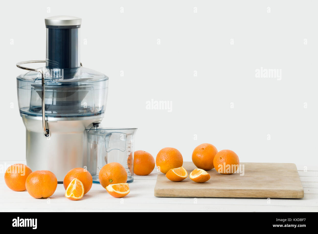 Modern electric juicer and fresh oranges, white background with copy space. - Stock Image