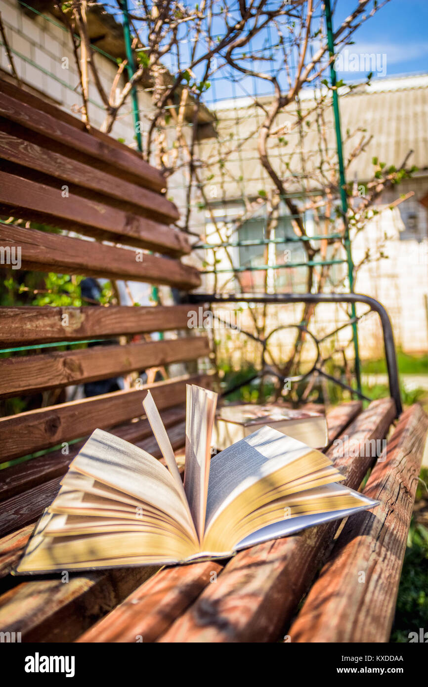 Open book on the wooden bench in the courtyard - Stock Image