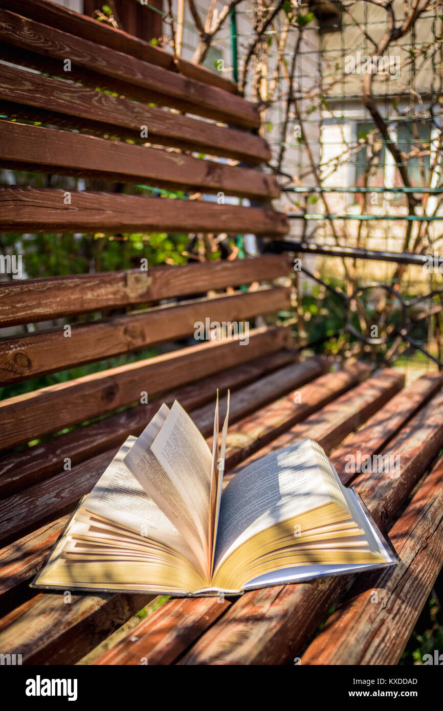 Open book lying on a wooden bench in the spring sunny day - Stock Image