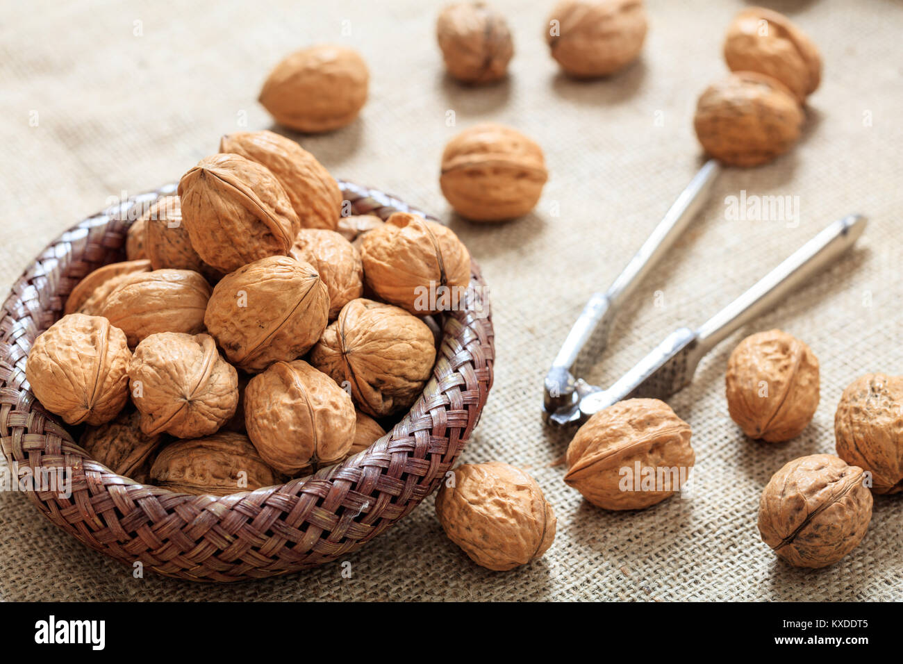 Walnuts in a small basket on a table - Stock Image
