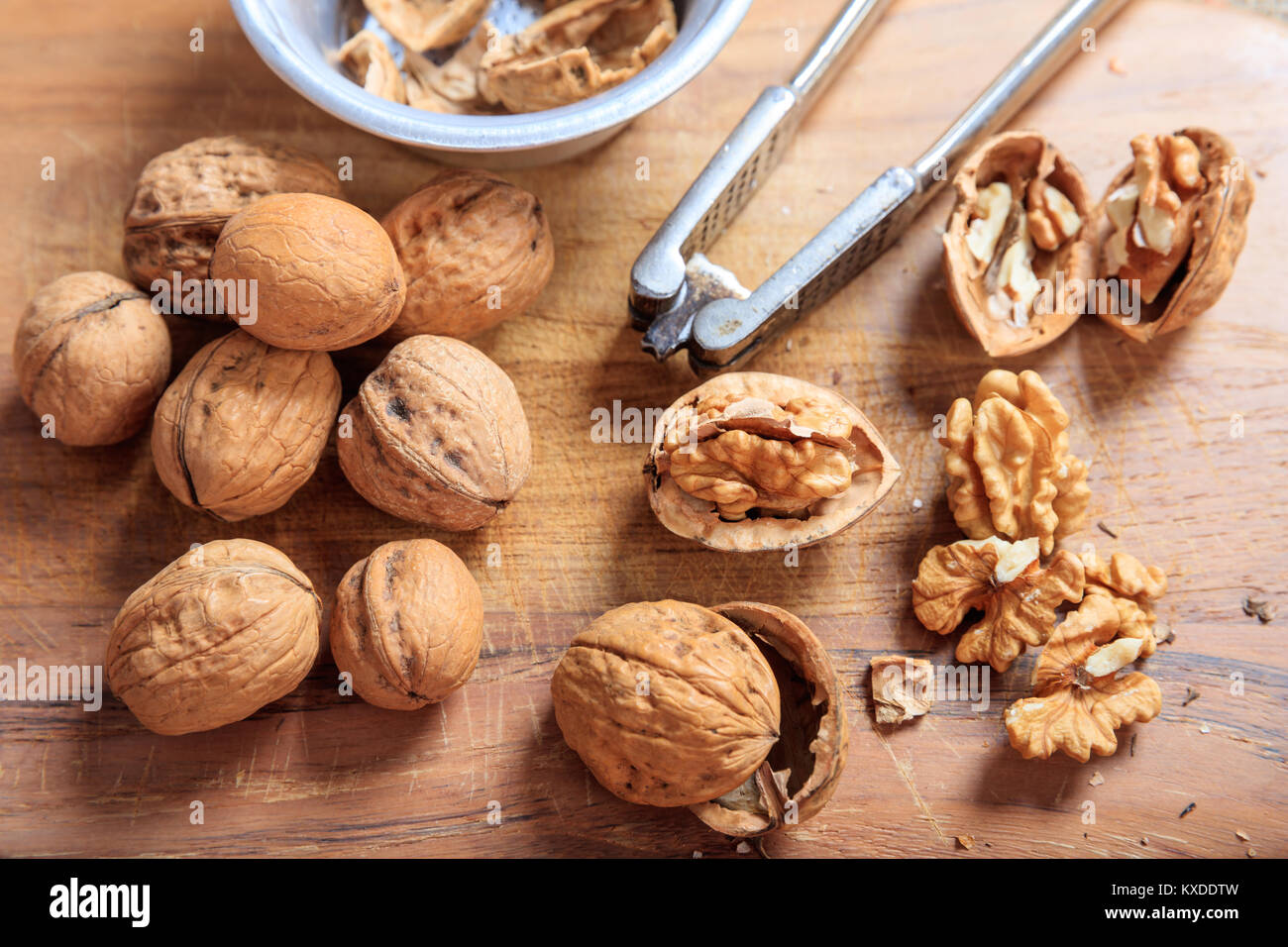 Walnuts and a nutcracker on a table Stock Photo