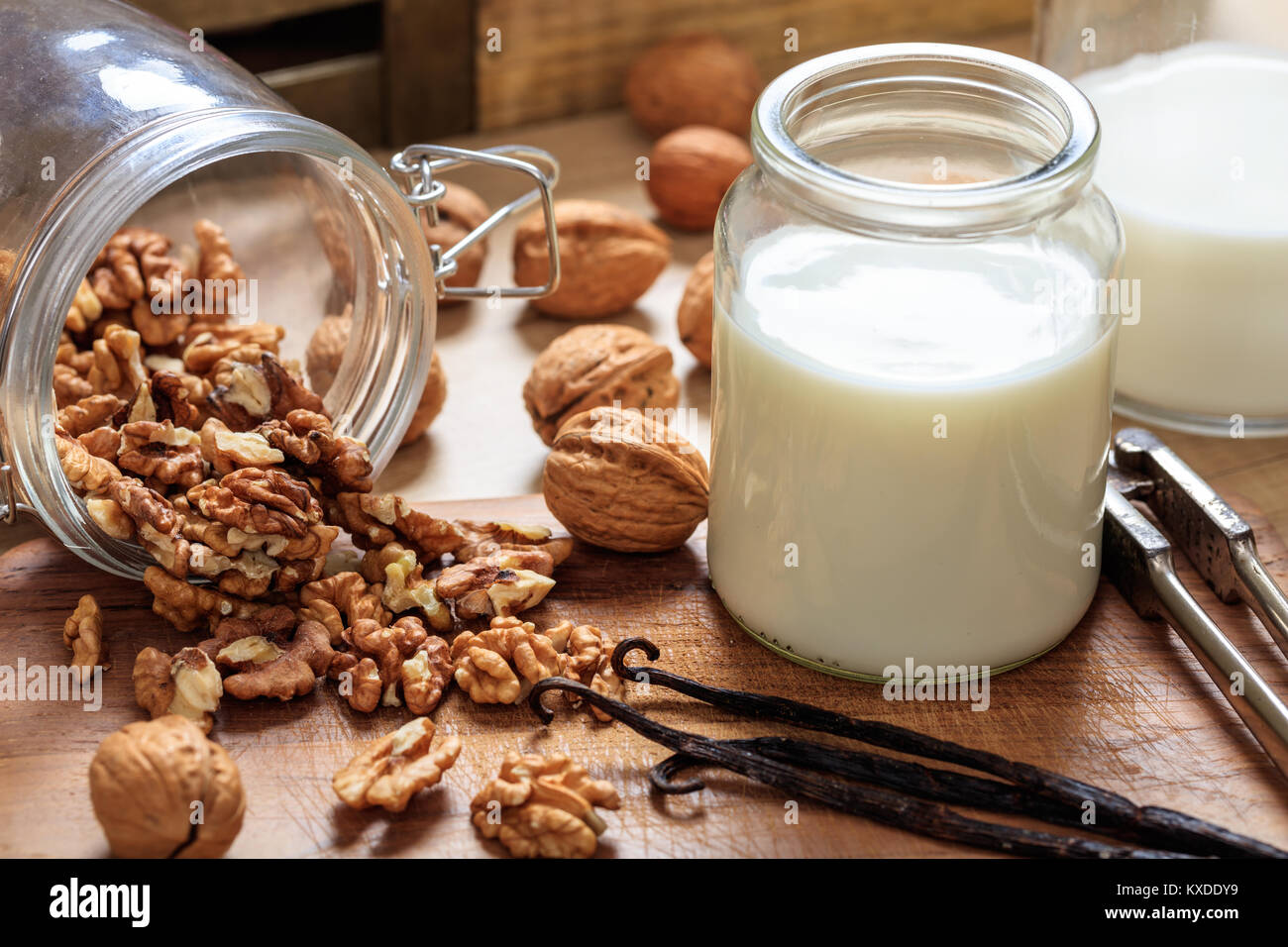 Vegan milk from walnuts on a wooden surface - Stock Image