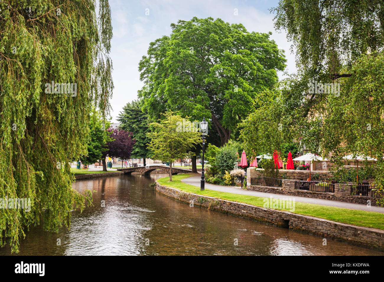 The River Windrush winding through the Cotswold village of Bourton-on-the-Water, Gloucestershire, England - Stock Image