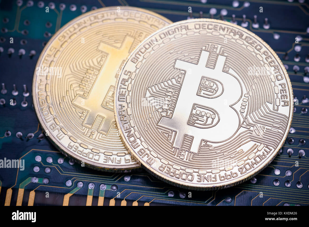 Symbol image digital currency, silver physical coins Bitcoin on printed circuit board Stock Photo