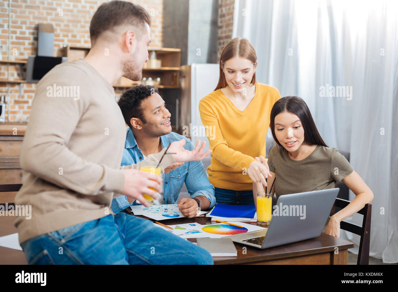 Surprised people smiling while their fellow student telling about her project - Stock Image