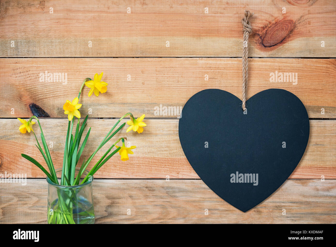 Wood planks with daffodils and a chalkboard in the shape of a  heart, love greeting card background with copy space - Stock Image