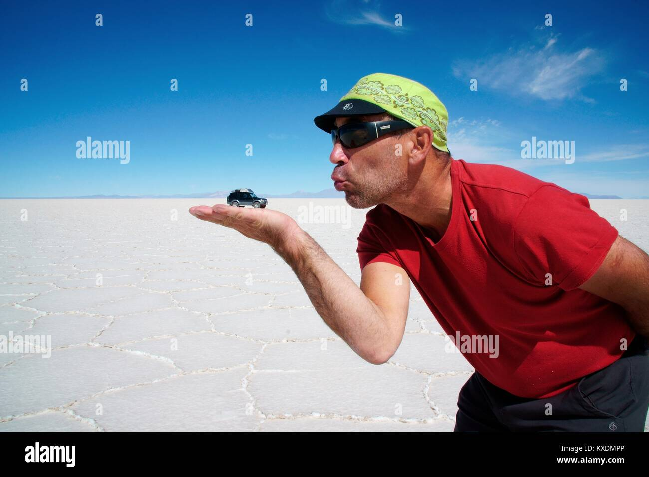 Optical illusion, man holds off-roader on hand, Salar de Uyuni, Uyuni, Potosi, Bolivia - Stock Image