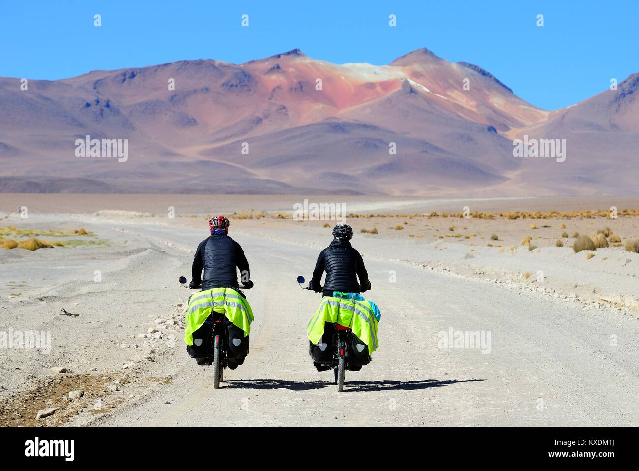 Two cyclists with luggage ride on the runway of the lagoon route, Reserva Nacional de Fauna Andina Eduardo Abaroa, - Stock Image