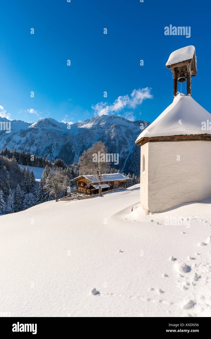 Mountain farm and chapel in winter, in Gerstruben, a former mountain farming village in the Dietersbach valley near Stock Photo