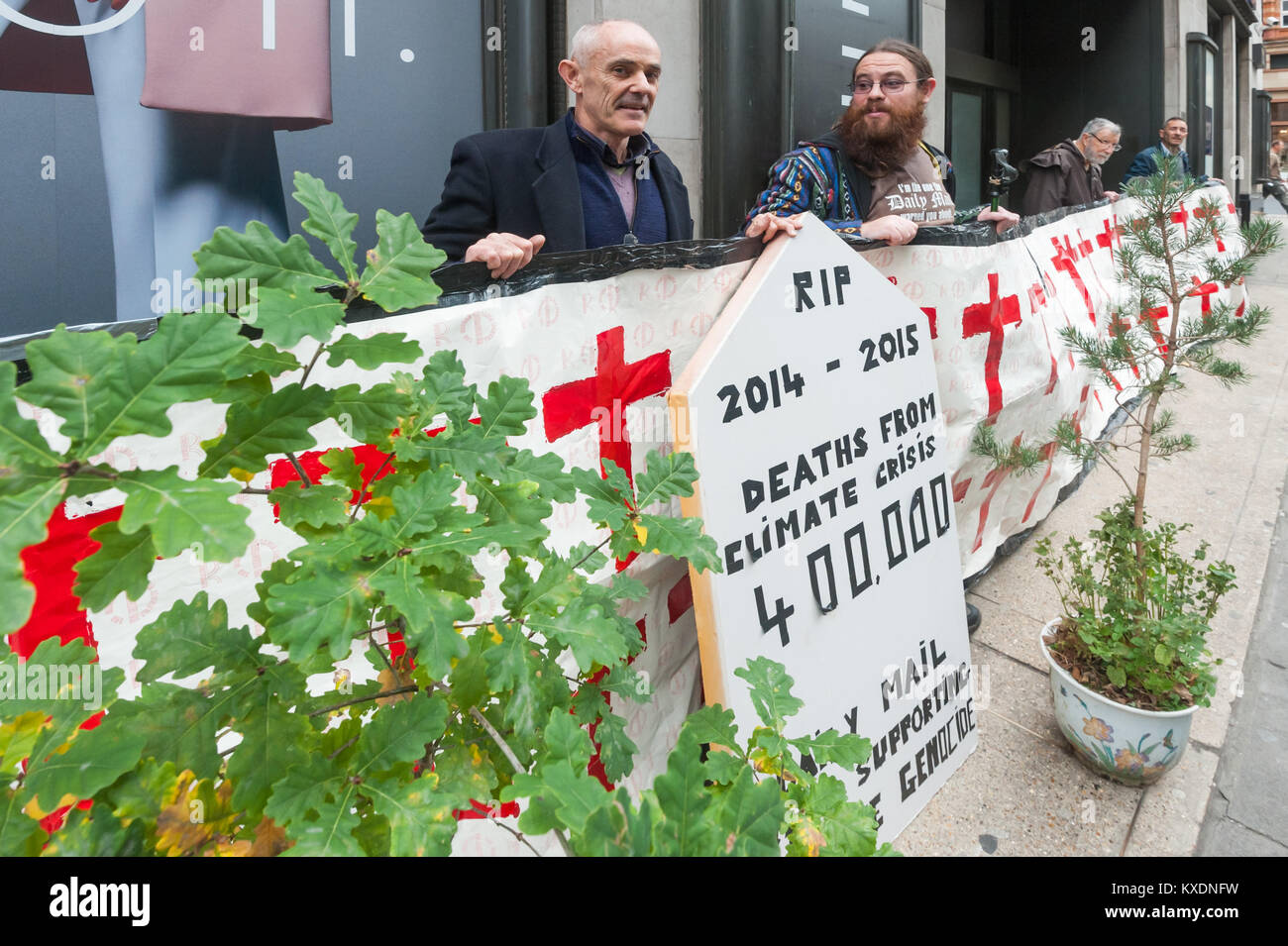 Occupy protesters brought banners,3 small trees and a tombstone to the Daily Mail in a protest to persuade it to Stock Photo