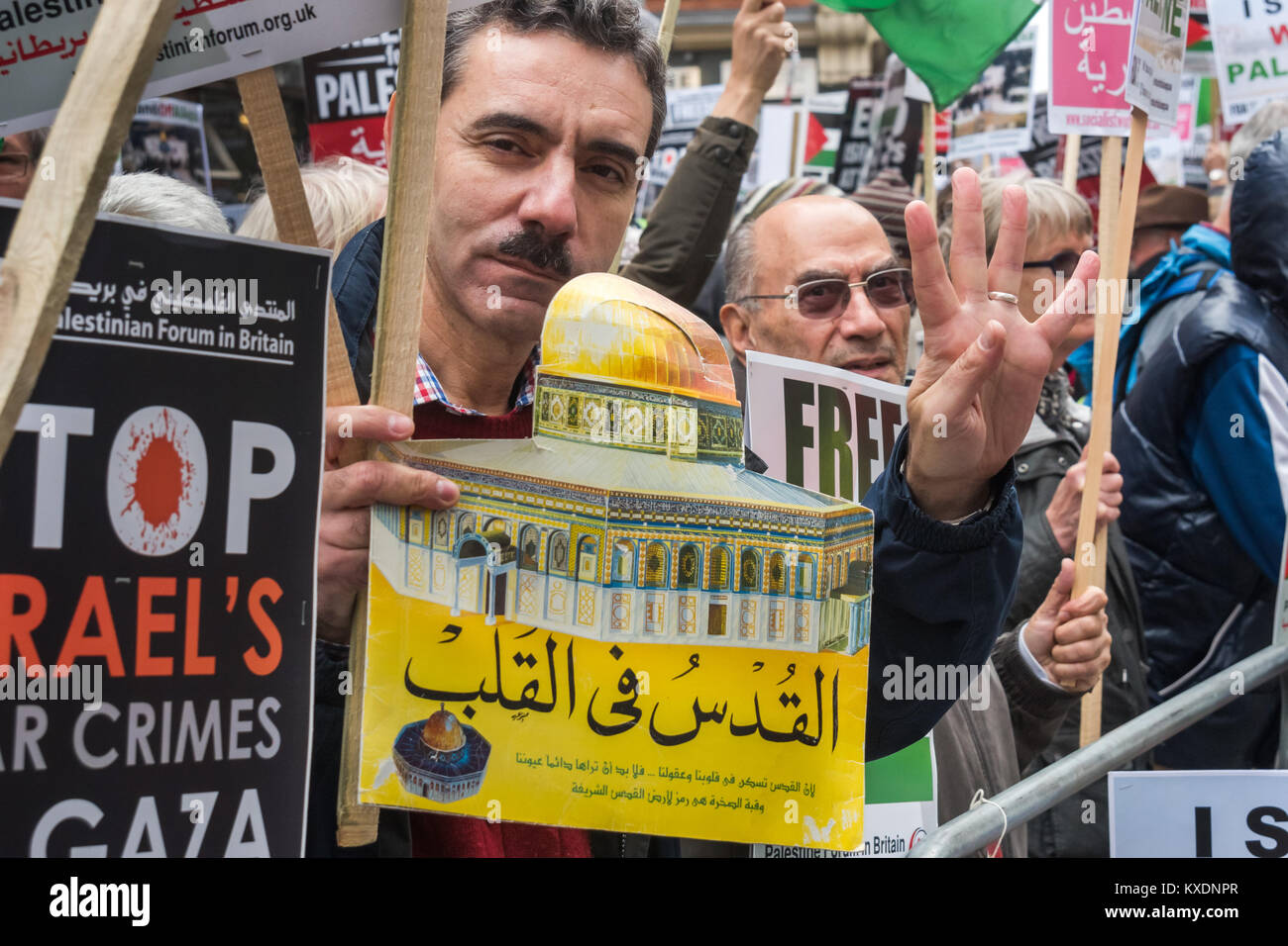 A man holds an image of the Al Aqsa mosque in Jerusalem at the protest at Israeli embassy in London calling for - Stock Image