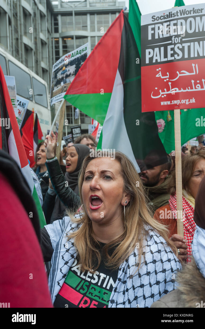 People with Palestinian flags and placards shout at protest at Israeli embassy in London calleing for an end to - Stock Image