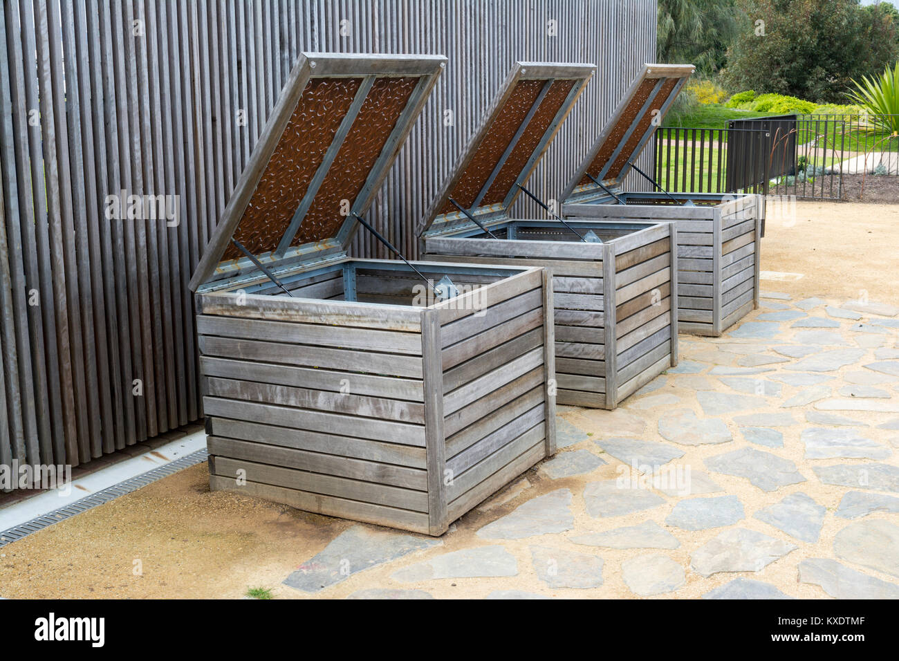 Three wooden compost bins  lined up with lids open ready to be used. Stock Photo