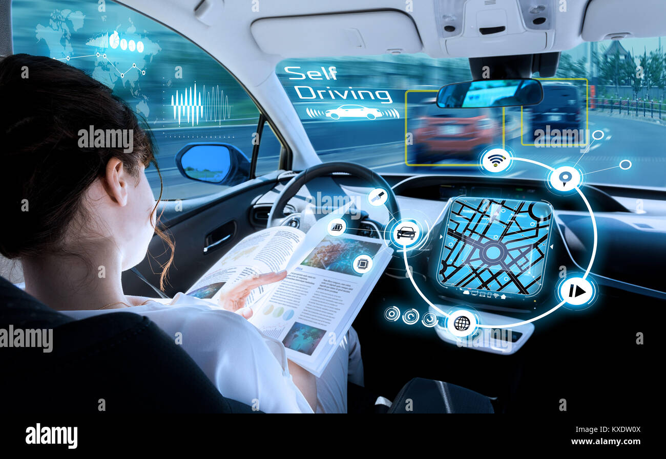 young woman reading a book in a autonomous car. driverless car. self driving vehicle. heads up display. automotive - Stock Image