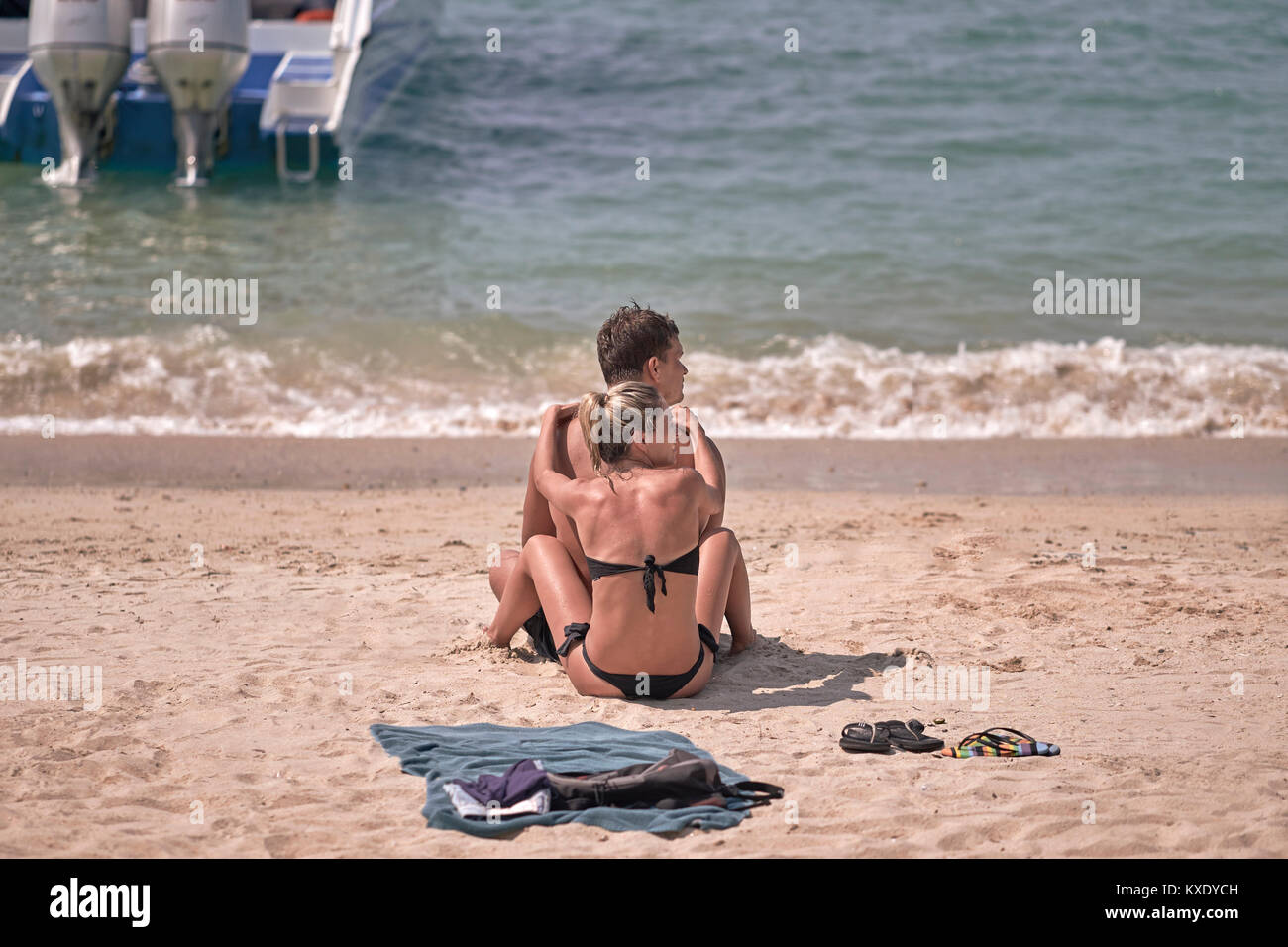 couple bonding in an affectionate coupling on the beach. Sunbathing and togetherness. Man and woman bonding. - Stock Image
