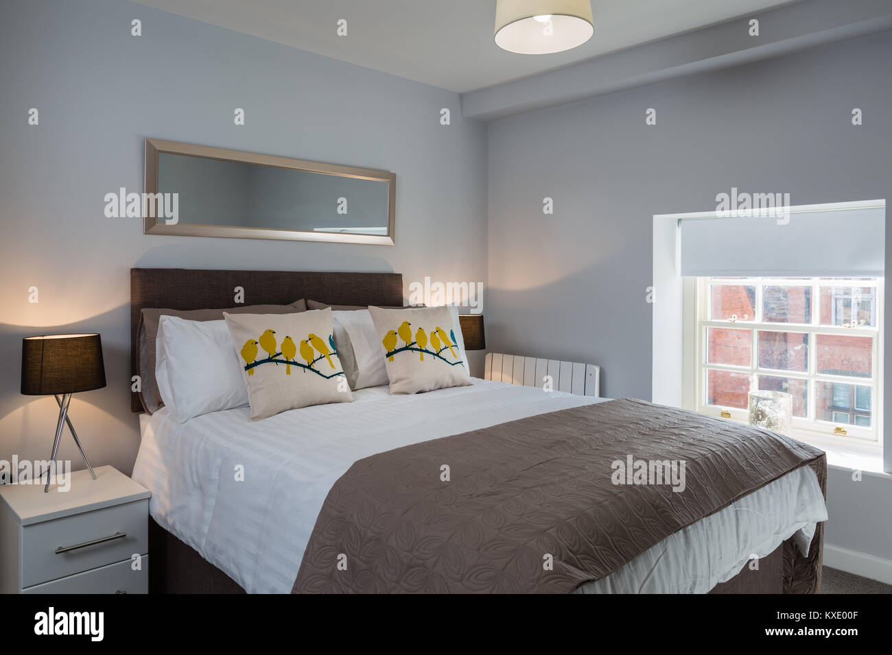 Master bedroom with large comfortable double bed and bedside cabinets with table lamps. - Stock Image