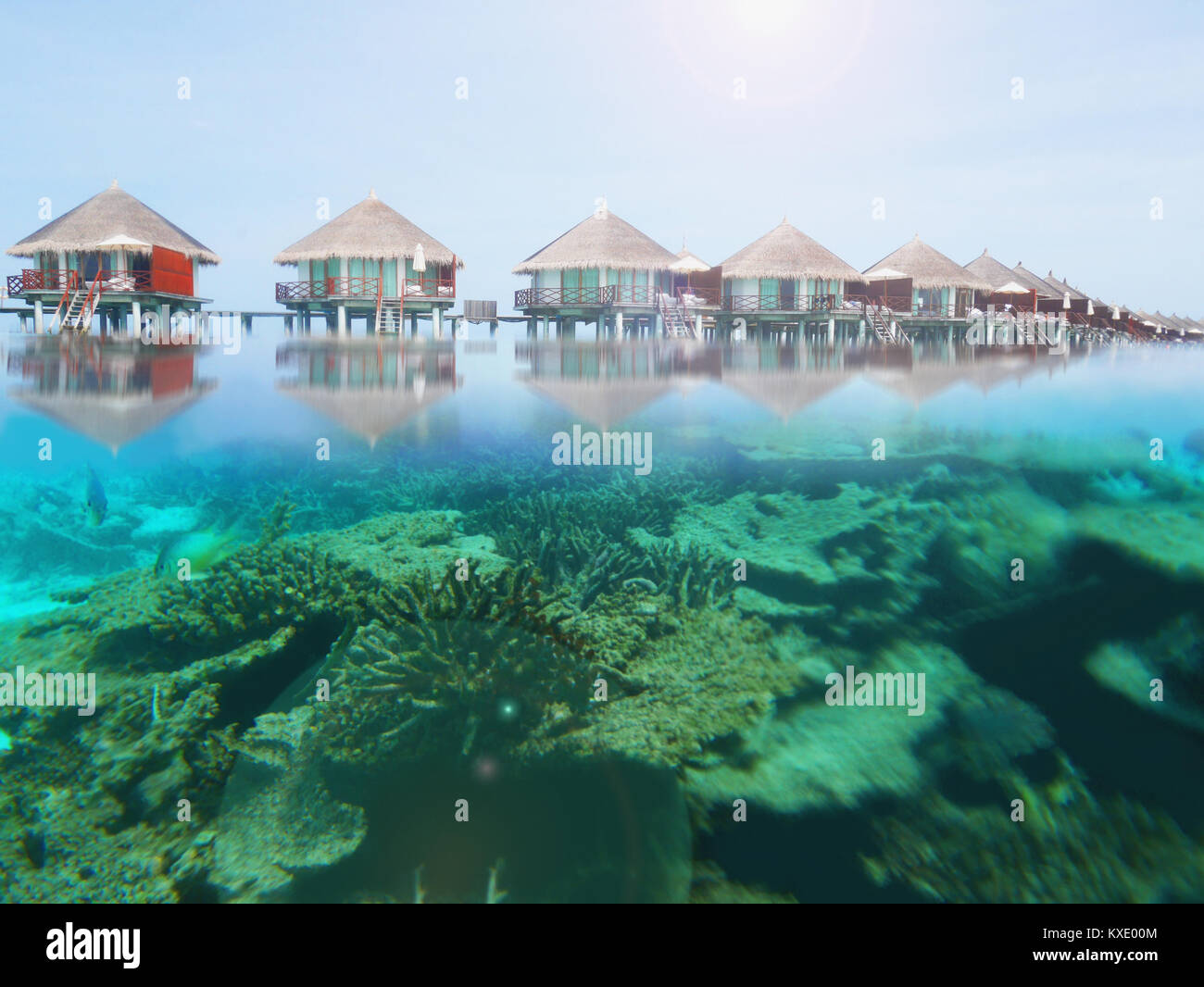 Line of water villa bungalows in a Maldives island resort with reflection on water and underwater tropical coral - Stock Image