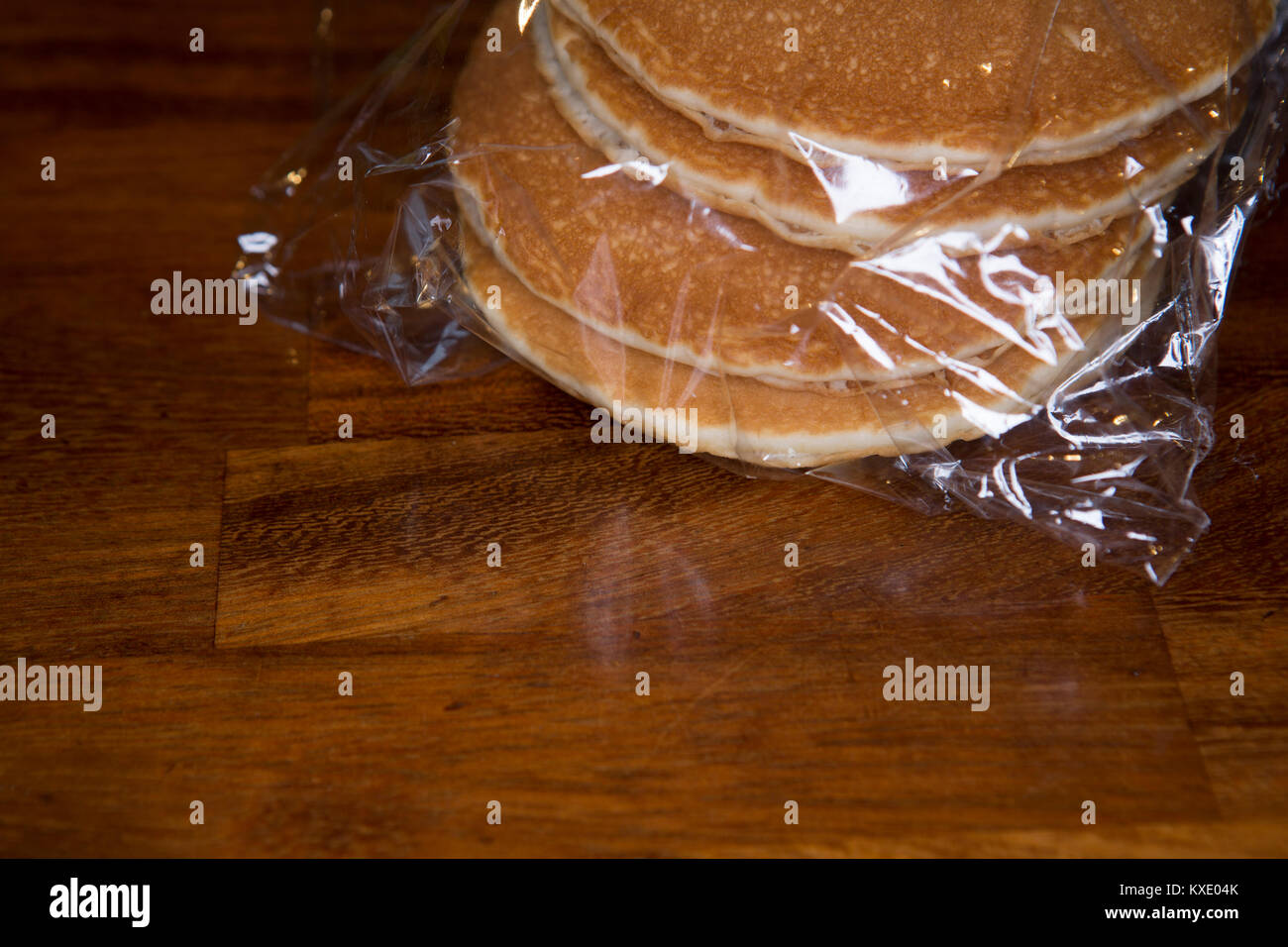 A packet of shop bought pancakes wrapped in cellophane and sitting on a kitchen work surface. - Stock Image