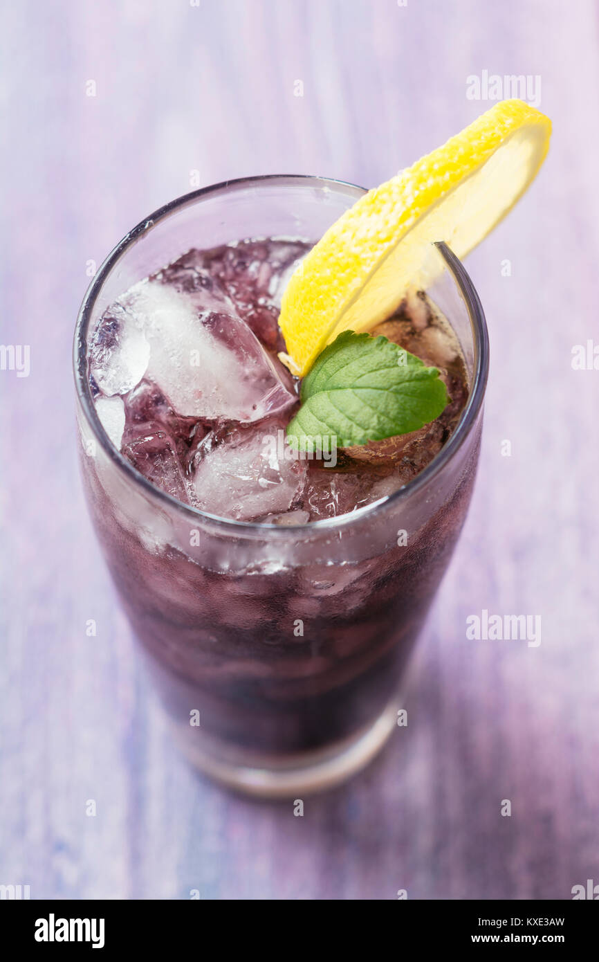 Long drink with elderberry and redcurrant vodka, elderberry syrup, sparkling water and lime juice Stock Photo