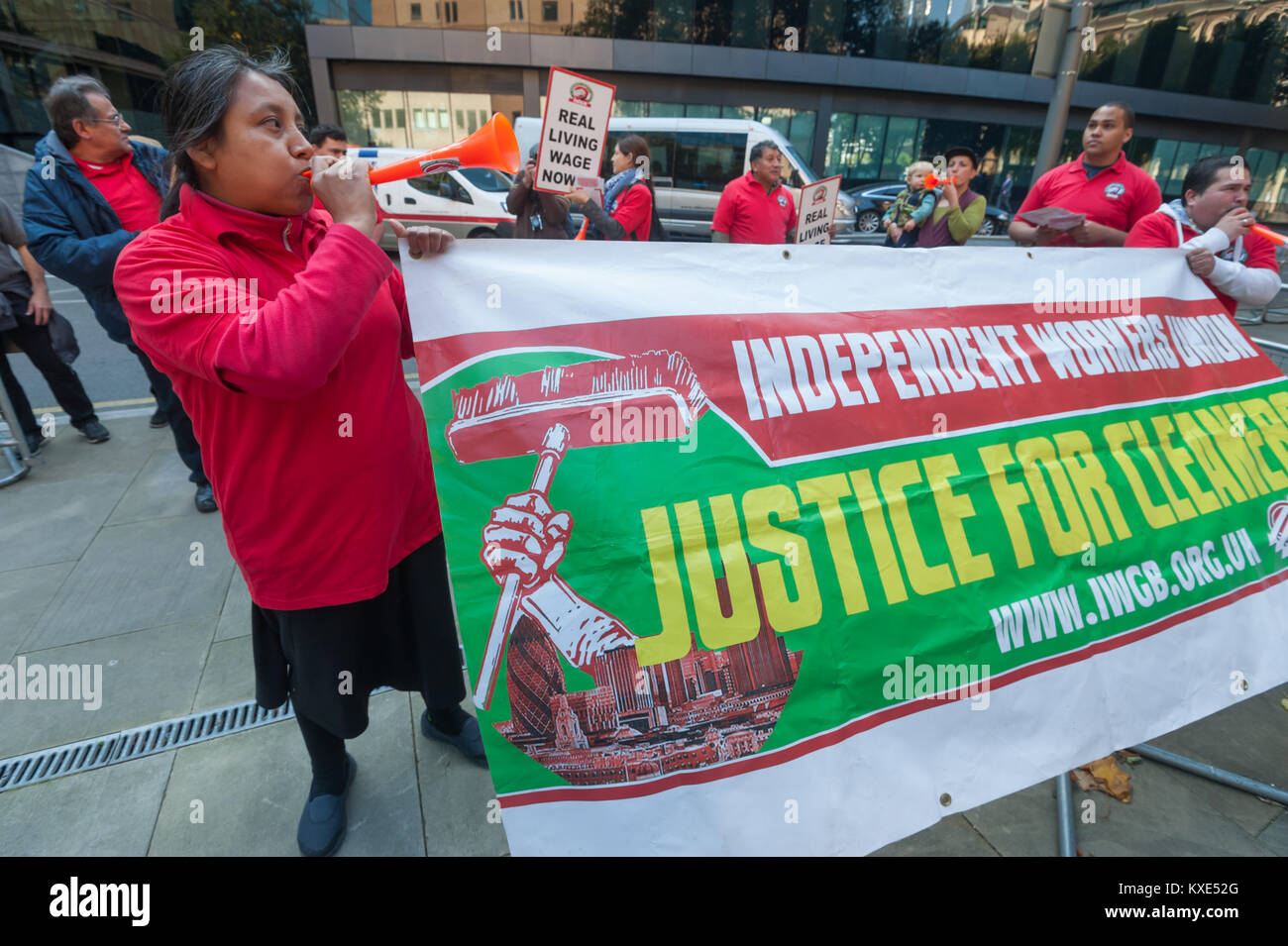 Cleaners hold the IWGB banner with its message 'Justice for Cleaners' outside Southwark Crown Court in the - Stock Image