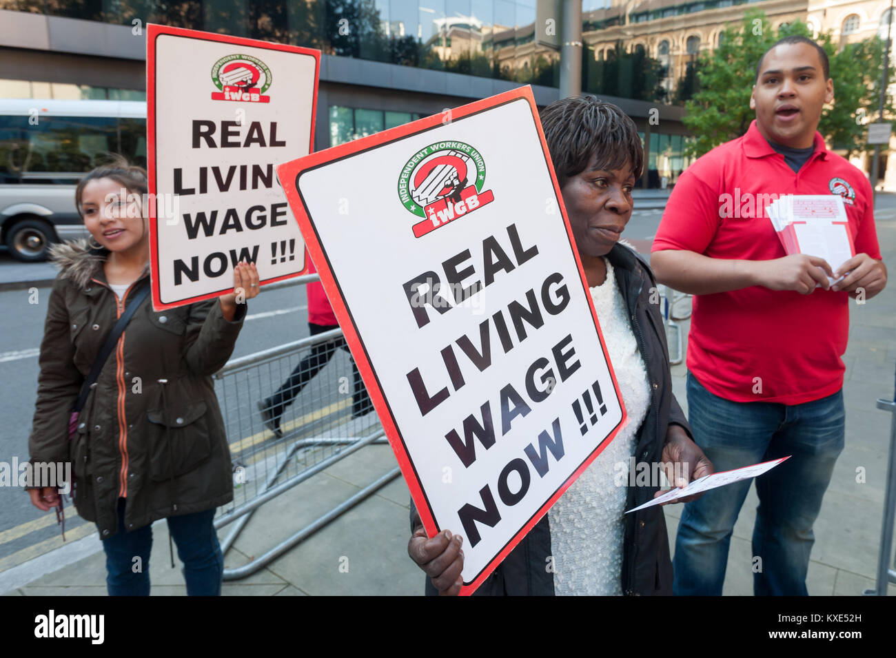 IWGB protesters hold placards 'Real Living Wage Now!!!' outside Southwark Crown Court in a protest for the - Stock Image