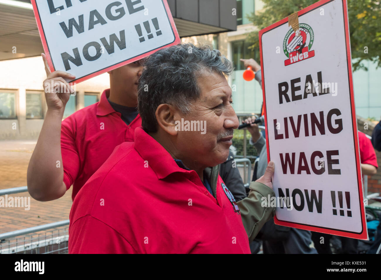 IWGB cleaners hold up placards 'Real Livng Wage Now!!' as the walk around in front of Southwark Crown Court - Stock Image