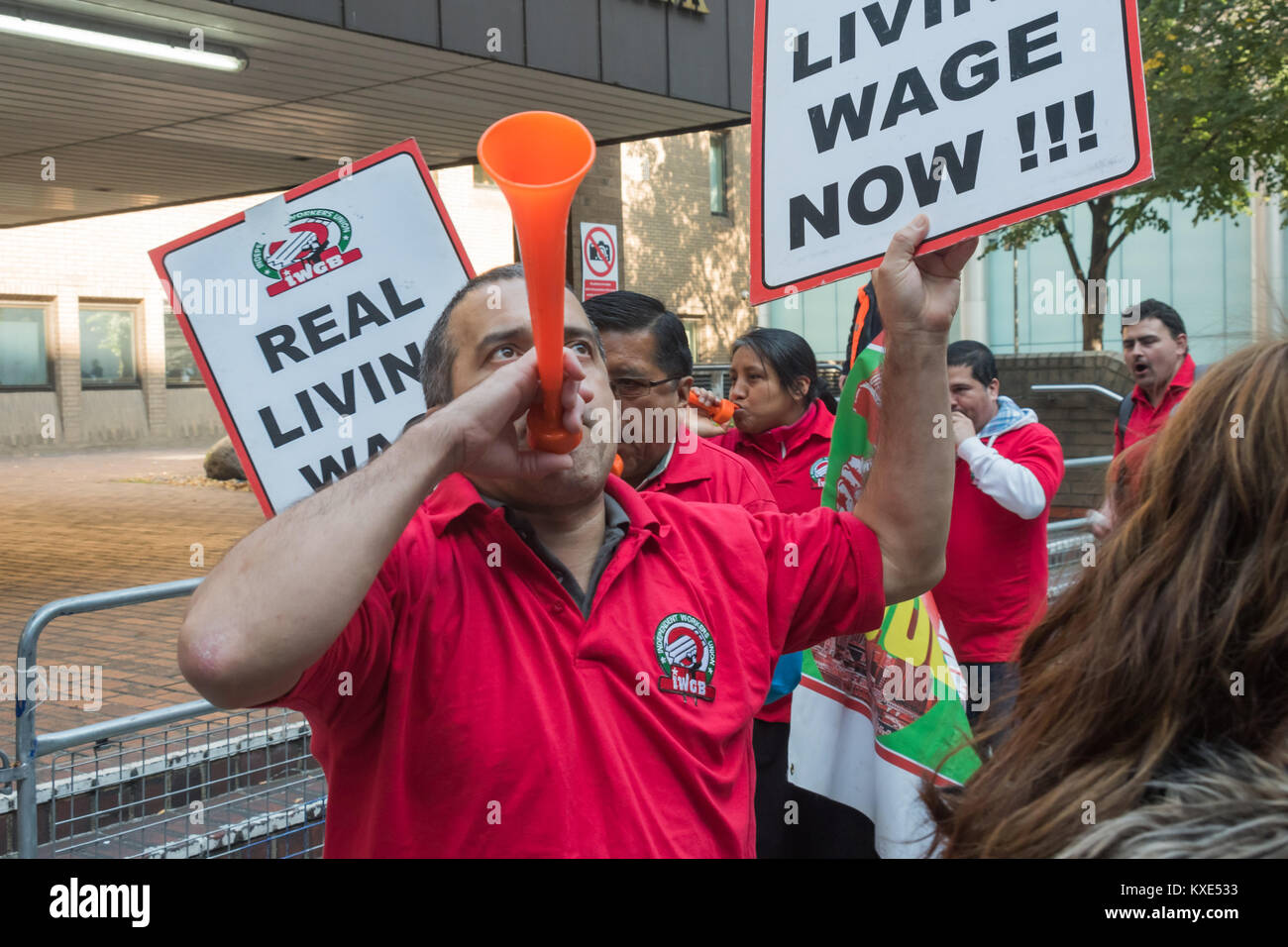 IWGB cleaners hold up placards 'Real Livng Wage Now!!' and blow horns as the walk around in front of Southwark - Stock Image